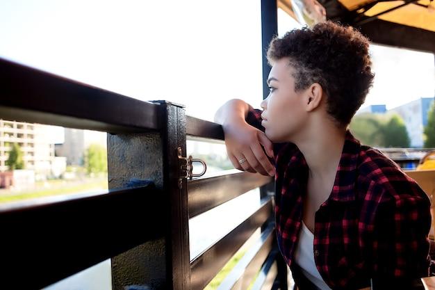 短い髪の美しいアフリカ系アメリカ人の女性は、夏のカフェで悲しいです。