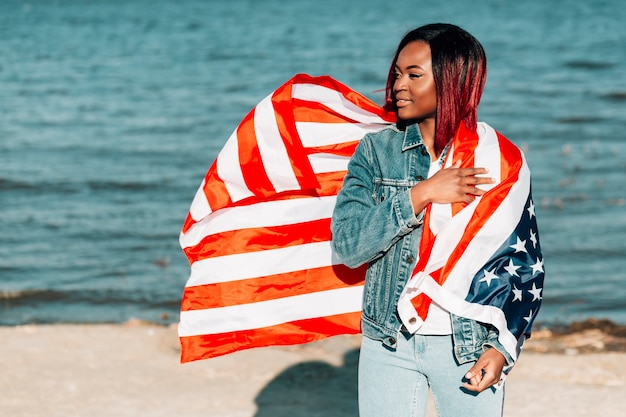 Beautiful african american woman with waving american flag