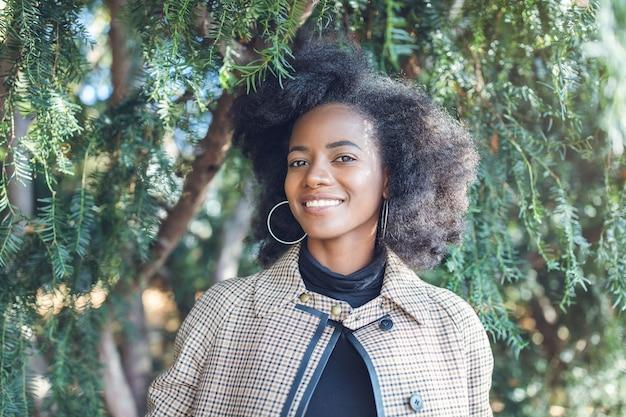 公園でスタイリッシュなコートを着たアフロヘアスタイルの美しいアフリカ系アメリカ人の若い女性
