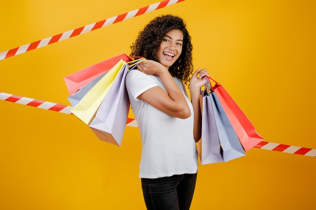 Beautiful african black woman with colorful shopping bags isolated over yellow with signal tape