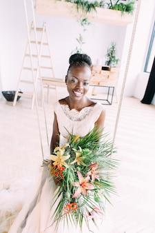 スタジオでトロピカルブーケを持つ美しいアフリカの花嫁