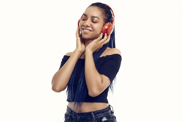 Beautiful african brunette teenage girl with dreadlocks listening music