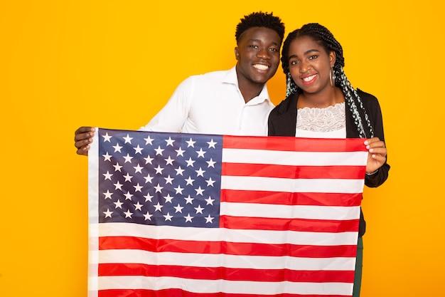 Красивая африканская пара мужчина и женщина с американским флагом