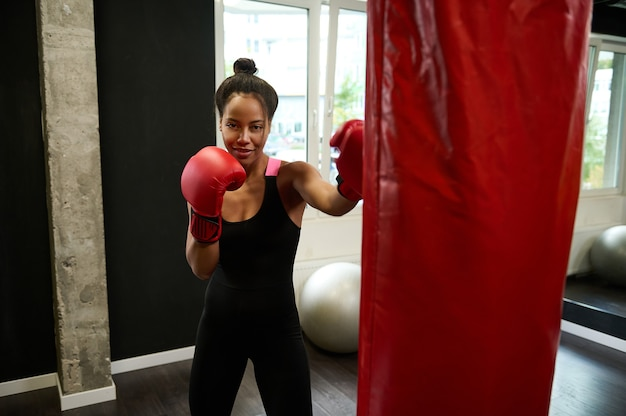 Beautiful african female athlete boxer wearing red boxing gloves strikes on punching bag, looks at camera while performing martial combat art at sports gym
