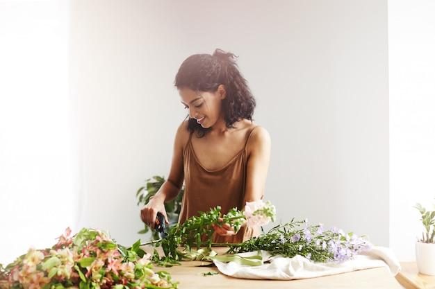白い壁を越えてフラワーショップで働くカッティング茎を笑顔の美しいアフリカ女性花屋。