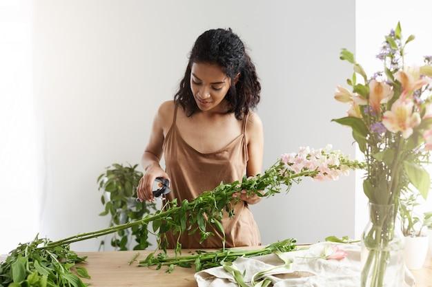 白い壁に花を扱う茎を笑顔の美しいアフリカ女性花屋。