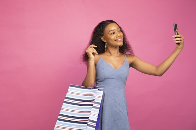 소셜미디어에서 쇼핑하는 동안 스마트폰으로 셀카를 찍는 아름다운 아프리카 여성