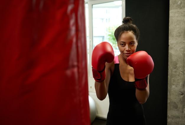 赤いボクシンググローブを着用し、ジムでサンドバッグを打つカメラでポーズをとる完璧な体格の美しいアフリカのフィット女性。格闘技中に一生懸命トレーニングする女性ボクサー