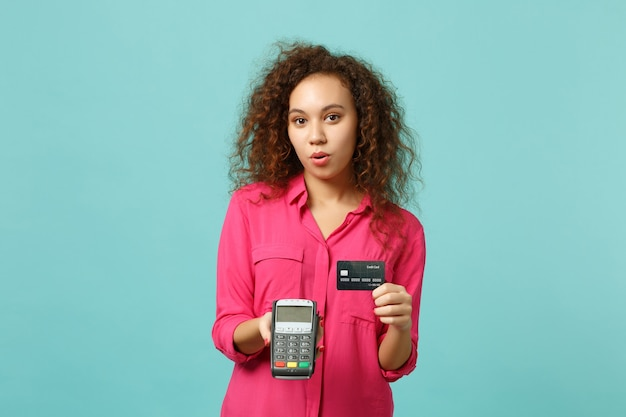 Beautiful african girl hold wireless modern bank payment terminal to process, acquire credit card payments isolated on blue turquoise background. people emotions lifestyle concept. mock up copy space.
