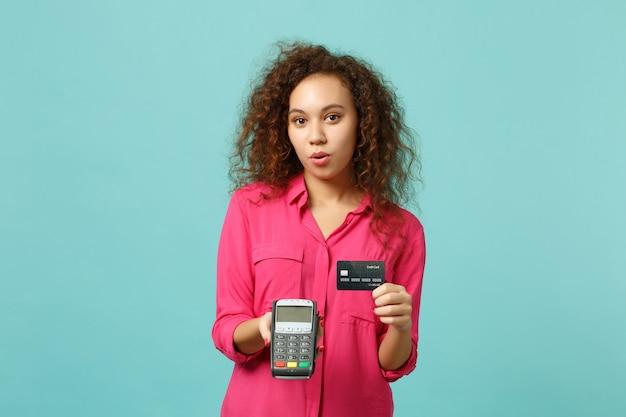美しいアフリカの女の子は、処理するためにワイヤレスのモダンな銀行決済端末を保持し、青いターコイズブルーの背景に分離されたクレジットカード決済を取得します。人々の感情のライフスタイルの概念。コピースペースをモックアップします。