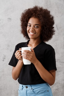 Beautiful african girl holding cup over light wall.