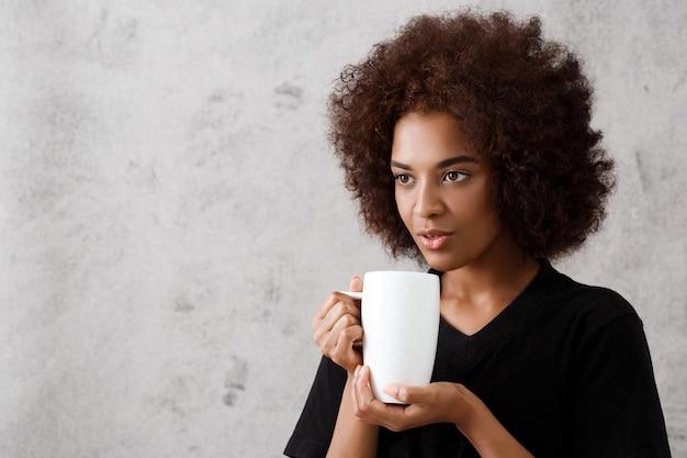 光の壁の上のカップを保持している美しいアフリカの女の子。