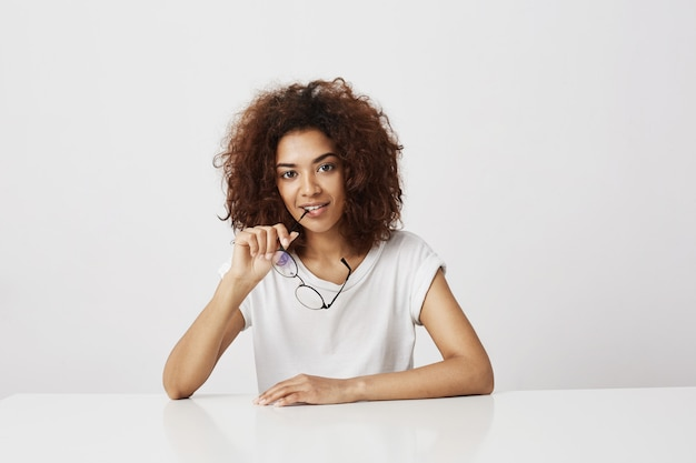 Beautiful african girl  holding glasses over white wall. copy space.