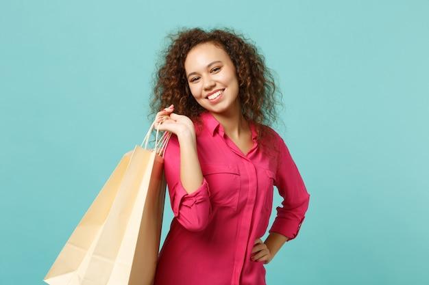 분홍색 캐주얼 옷을 입은 아름다운 아프리카 소녀는 파란색 청록색 벽 배경에서 쇼핑한 후 구매한 패키지 가방을 들고 있습니다. 사람들은 진심 어린 감정 라이프 스타일 개념입니다. 복사 공간을 비웃습니다.