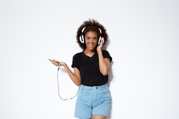 Beautiful african girl listening music in headphones over white wall.