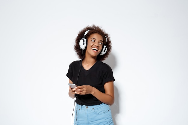 Beautiful african girl listening music in headphones over white wall