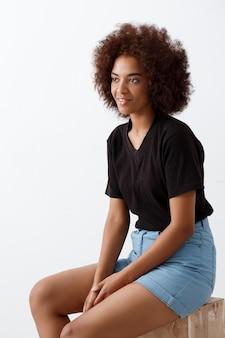 Bella ragazza africana che si siede e che sorride sopra la parete leggera.