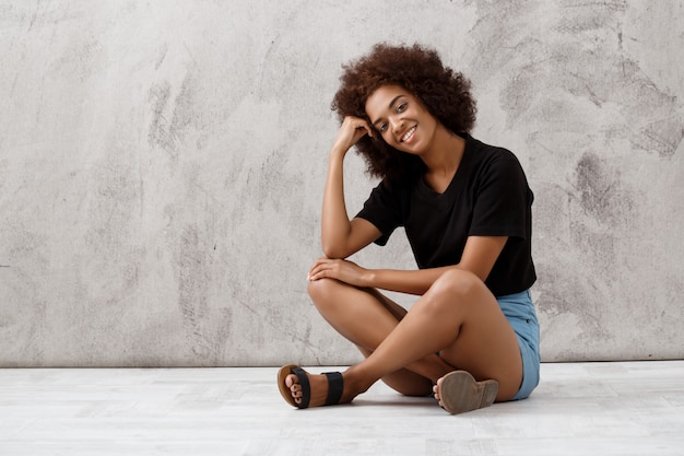 Beautiful african girl sitting and smiling over light wall.