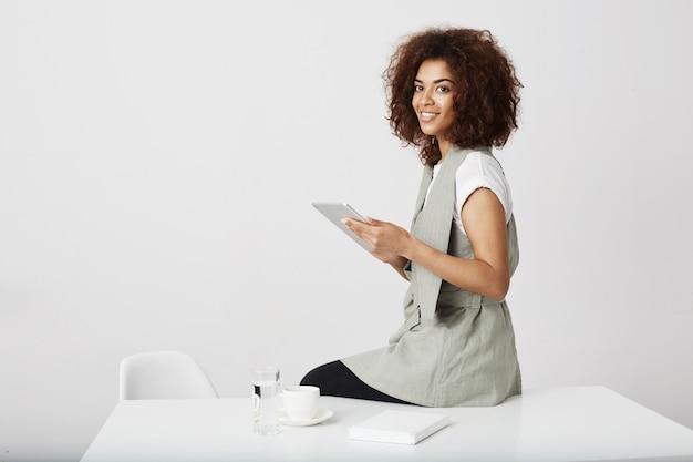 職場に座って持株タブレットを笑っている美しいアフリカの女の子。コピースペース。
