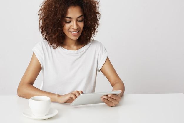 白い壁にタブレットを見て笑っている美しいアフリカの女の子。コピースペース。