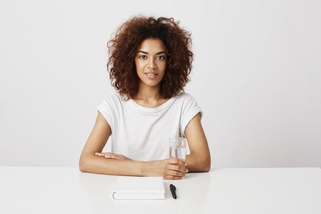 白い壁に座って笑っている美しいアフリカの女の子。コピースペース。