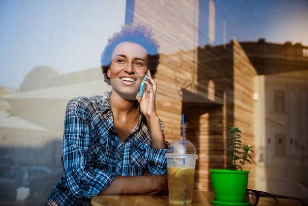 笑みを浮かべて、電話で話して、カフェに座って美しいアフリカの女の子。外から撮影。