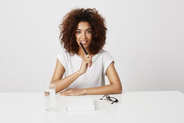 白い壁の上のテーブルに座って考えて笑っている美しいアフリカの女の子。コピースペース