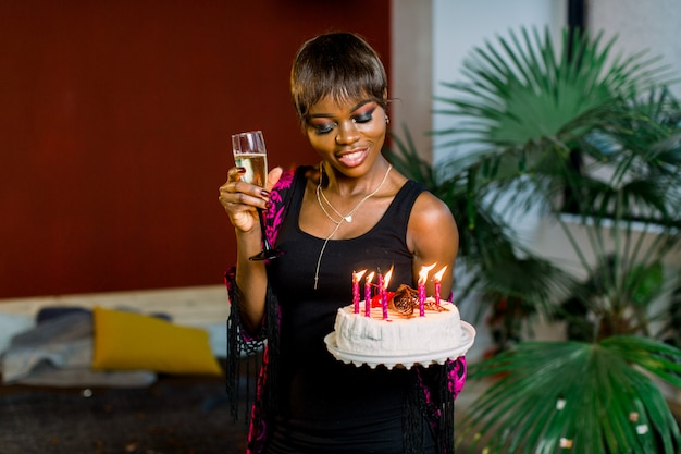 Beautiful african girl with birthday cake and with lighting candles and champagne