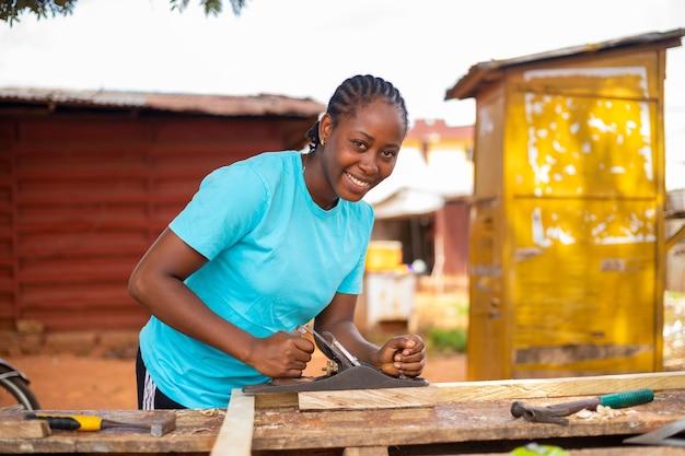 아름다운 아프리카 여성이 잭 비행기를 사용하여 목재를 크기로 자르면서 미소를 짓습니다