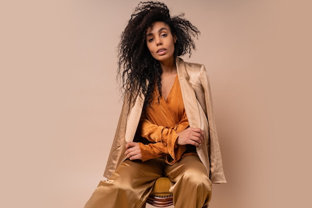 Beautiful  african model with perfect curly hairs in elegant orange blouse and silk pants sitting on vintage chair  beige wall.