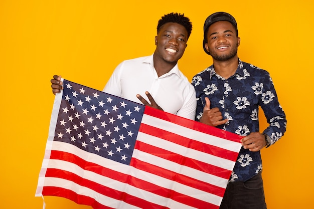 Beautiful african people with american flag on yellow background