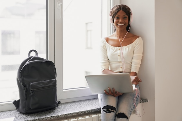 Beautiful african student girl sitting on windowsill with laptop on knees and smiling at camera. pretty female in white blouse and jeans listening music from big headphones at university corridor.