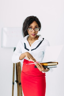 Beautiful african teacher in white shirt and red skirt holding books and documents