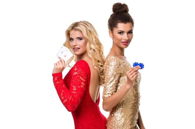 아름 다운 아프리카 여자와 저녁 복장에 긴 밝은 금발 머리를 가진 백인 젊은 여자. 카드 놀이와 칩을 들고. 외딴. 포커