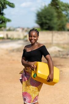 黄色い水の受信者を保持している美しいアフリカの女性