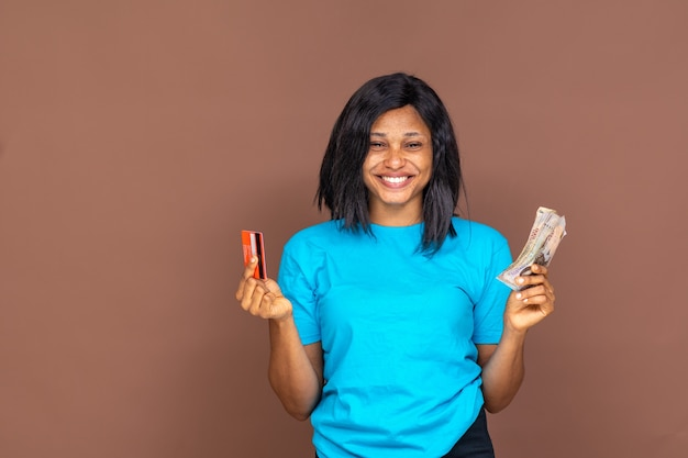 Beautiful african woman holding cash in one had and a credit card in the other hand