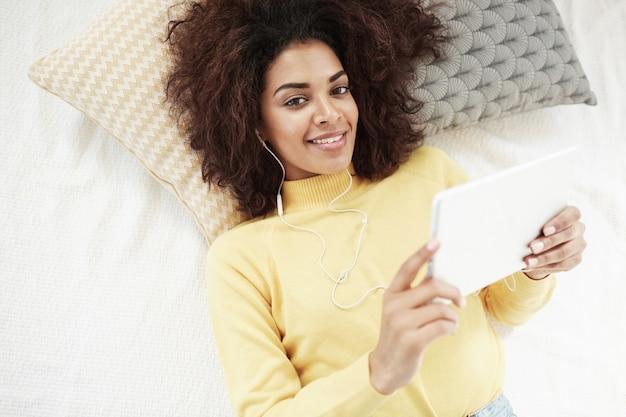 Красивая африканская женщина в наушниках держа таблетку лежа на усмехаться кровати.