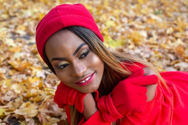 Красивая африканская женщина в красной одежде отдыхает в осенних листьях