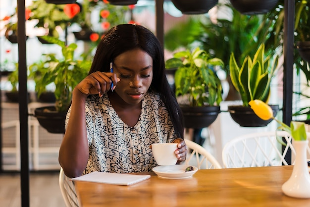 美しいアフリカの女性がカフェテリアでメモを取っています