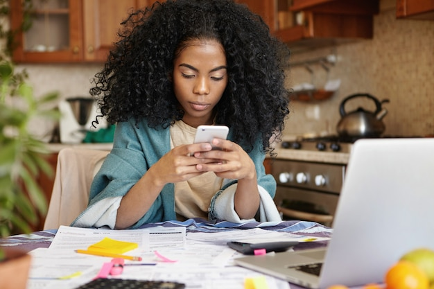 Beautiful african woman making phone call while calculating bills in kitchen, surrounded with papers. indoor shot of unhappy young lady using mobile in front of laptop and analyzing home finances