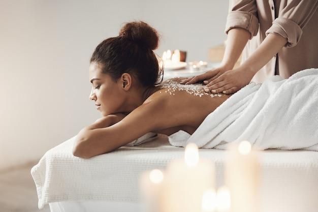 Красивая африканская женщина отдыхая наслаждающся массажем здоровья курорта с солью моря.