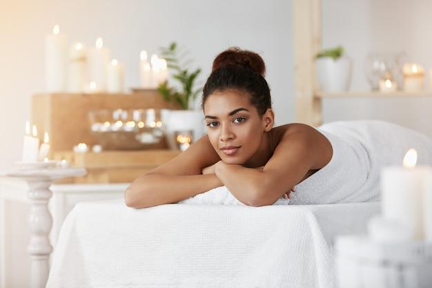 Rilassamento di riposo della bella donna africana nel salone della stazione termale