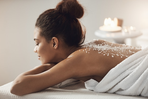 Beautiful african woman resting relaxing with sea salt on back in spa salon.