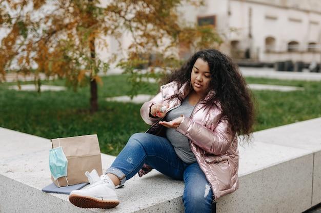 新鮮な空気の上に座って、手に消毒剤を使用している美しいアフリカの女性。人、衛生、安全の概念。