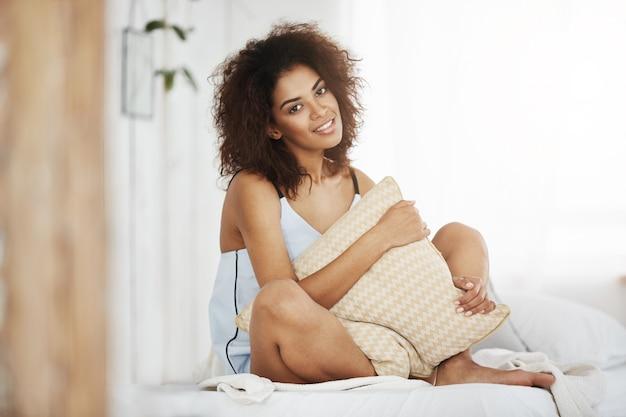 Bella donna africana in cuscino sorridente della tenuta degli indumenti da notte che si siede sul letto a casa.