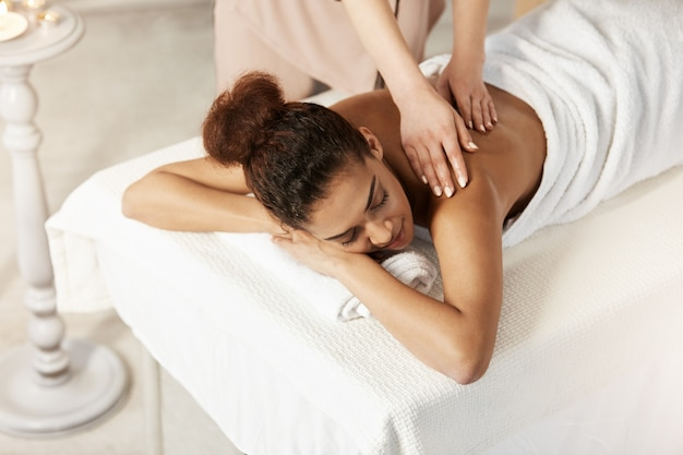 Beautiful african woman smiling enjoying massage with closed eyes in spa salon.