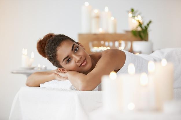 Отдыхать красивой африканской женщины усмехаясь отдыхающ в салоне курорта.