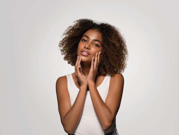 Красивая африканская женщина в белой футболке портрет афро-стрижка, касаясь ее лица цвет фона серый