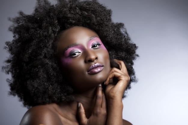 Красивая африканская женщина с большими кудрявыми афро и цветами в волосах