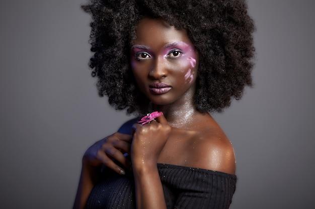 Bella donna africana con grandi ricci afro e fiori tra i capelli